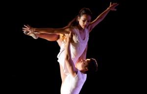 a dancer lifts another dancer overhead.