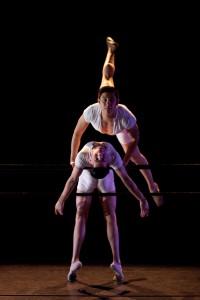 A dancer jumping above another dancer.